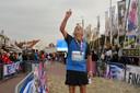 Jan Bostelaar wijst naar de hemel nadat hij de Kustmarathon heeft gelopen voor Lein Lievense. Het duo werkte vanaf het begin samen tijdens het evenement.