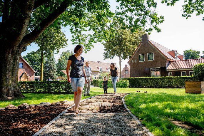 Het pleintje aan de Valendries is inmiddels aangekleed met een insectenhotel, waterspeelplaats en een blotevoetenpad Op de foto Frans Derks, Iris Stevens (met korte spijkerbroek aan) en Lieke Vergunst met de dochtertje.