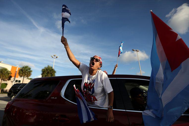 Een vrouw in Miami rijdt langs een restaurant dat populair is onder de Cubaanse diaspora in die stad en wuift met een Cubaanse vlag.  Beeld REUTERS