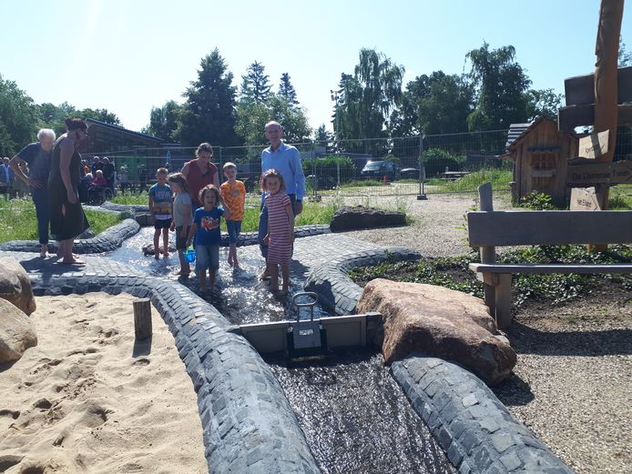 Wethouder Dorus Klomberg met kinderen op blote voeten op het nieuwe waterpad in de Dierense Speeltuin. Voor hem Linde, naast hem Luke.