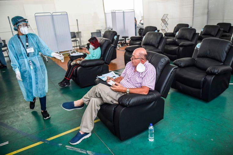 Een vrijwilliger zit in de obervatieruimte nadat hij het Sinopharm-vaccin heeft gekregen, in Lima, Peru. Beeld AFP