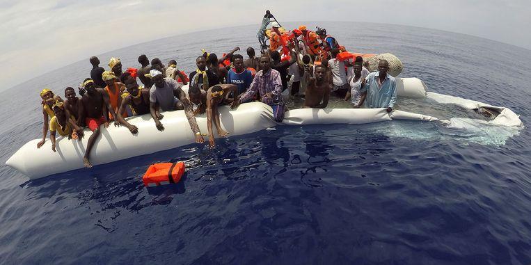 Migranten worden voor de Libische kust gered door de ngo Save the Children. Beeld REUTERS