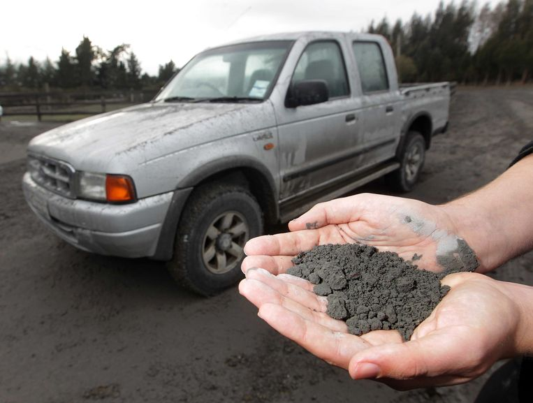 A man holds a handful of volcanic ashes that fell on a property in Rangipo near the base of Mt Tongariro, New Zealand after an eruption Tuesday, Aug. 7, 2012. The volcano in New Zealand's central North Island has erupted for the first time in more than a century, sending out an ash cloud that is causing road closures and the cancellation of some domestic flights. (AP Photo/New Zealand Herald, Alan Gibson) AUSTRALIA OUT, NEW ZEALAND OUT Beeld AP