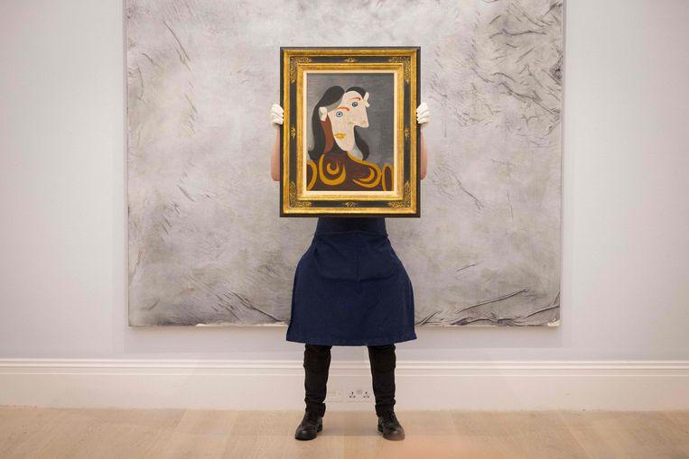 Een medewerker van Sotheby's in Londen poseert, voorafgaand aan de grote zomerveiling, met een schilderij van Pablo Picasso. Beeld AFP