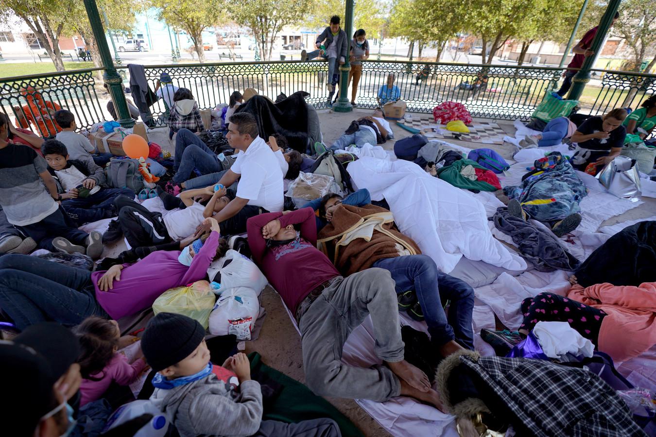 Door de VS uitgezette migranten rusten uit in een park in Mexico.