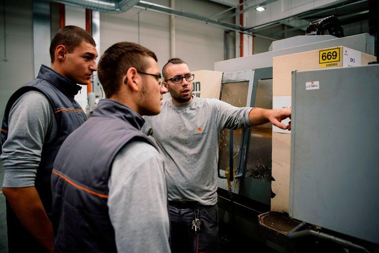 Twee jongeren krijgen instructies in een fabriek. Beeld AFP