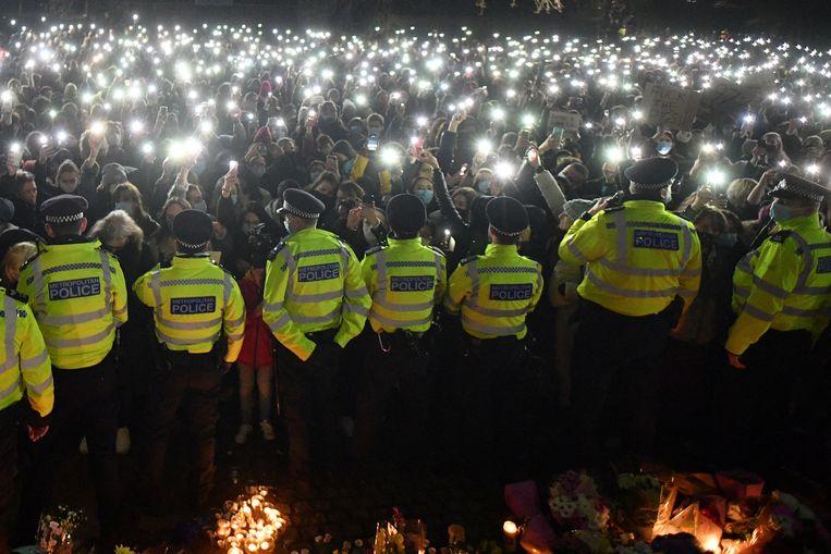 Een politiekordon blokkeert de rouwenden, die met het licht op hun telefoon hun medeleven betuigen aan de vermoorde Sarah Everard.  Beeld AFP