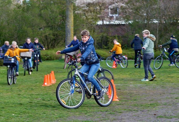 Buitenles dag bij Kidion in Volkel. Op de foto leggen leerlingen van groep 7 een parcours af op de fiets.  (Rechts juf Femke Raijmakers)