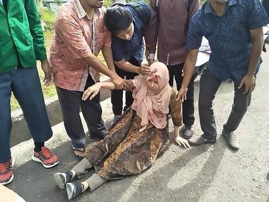 Voorbijgangers bekommeren zich om een gewonde vrouw in Ambon.
