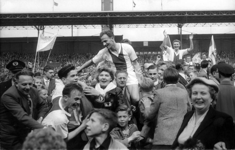 Willy Schmidt, op handen gedragen door Ajax-supporters na de landstitel in 1957. Beeld ANP