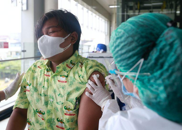 Een student krijgt een coronavaccin toegediend in Jakarta, Indonesië. Beeld REUTERS