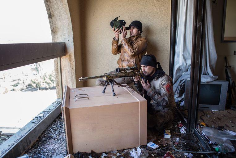 ► Ali Kareem en Amjad Kadham van de Iraakse 'Gouden Divisie' houden vanuit het Ninevé International Hotel de westoever van Mosoel in de gaten, waar IS nog altijd heerst. Beeld Hawre Khalid