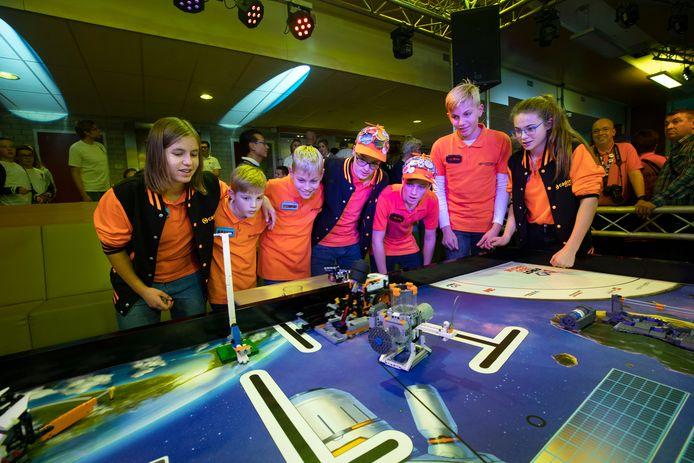 Een team volgt de verrichtingen van hun robot aan één van de robottafels.