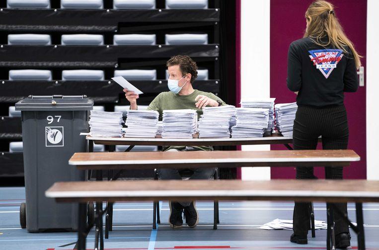 Stemmentellers sorteren de briefstemmen uit de gemeente Nijmegen en gooien de stemmen in de stembussen. Beeld ANP