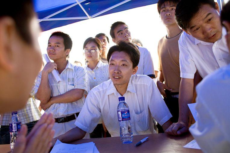 Een werkzoekende man voert een sollicitatiegesprek met een schoenenproducent op de banenmarkt in Dongguan. Beeld Getty