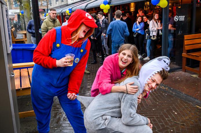 """Yasmijn als Mario (links), Isa in haar badjas en Joost """"De Haai"""" vermaken zich prima ondanks de wind en regen."""