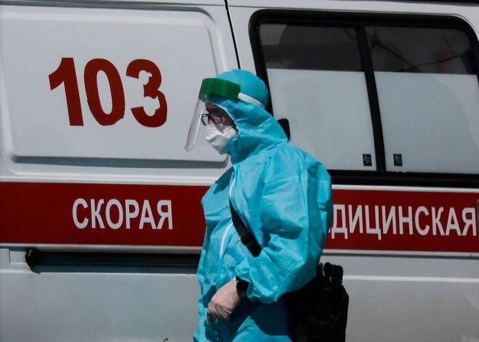 Un médecin spécialiste passe devant une ambulance à l'extérieur d'un hôpital pour patients infectés par le COVID-19 à Moscou, Russie, le 16 juin 2021.