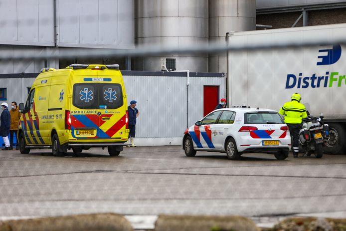 Medewerkers van slachterij Vion verzamelen zich buiten voor de ambulance waarin hun college naar het ziekenhuis zal worden vervoerd.