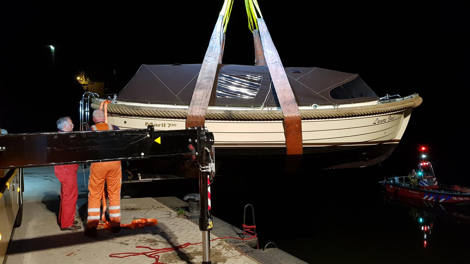 Het bootje wordt door de berger uit het water getild.