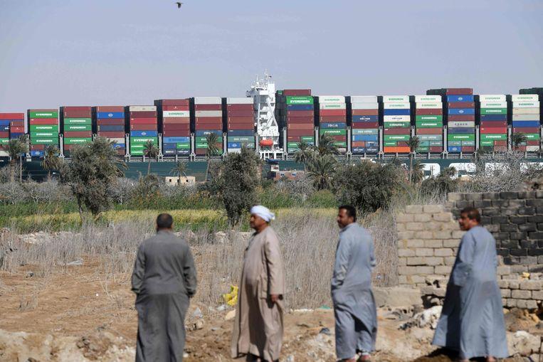 Egyptenaren kijken toe hoe het containerschip 'Ever Given' wordt vlotgetrokken op het Suezkanaal. Beeld AFP
