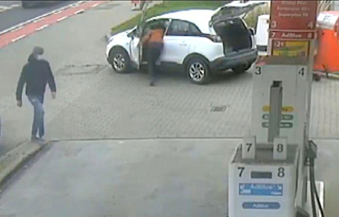 Eén verdachte steelt de handtas terwijl zijn kompaan (links met donkere jas) op een afstand blijft. De broer en zus bevinden zich op dat moment rechts achter hun auto.