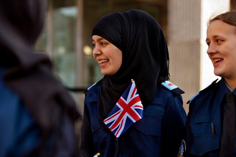 Leden van de Britse de geüniformeerde vrijwillige politiestagiairs, de VPC, mogen net als politieagenten een hoofddoek of een tulband dragen. In Groot-Brittannië wordt het dragen van deze geloofsuitingen niet gezien als een aantasting van de neutraliteit van de politie. Beeld Corbis via Getty Images