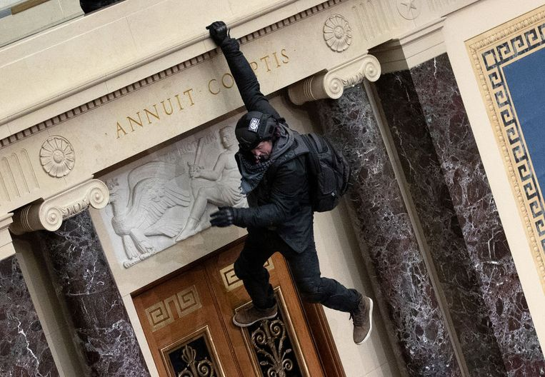 Demonstranten dringen het gebouw binnen en klauteren de Senaat in via het balkon.  Beeld Getty Images