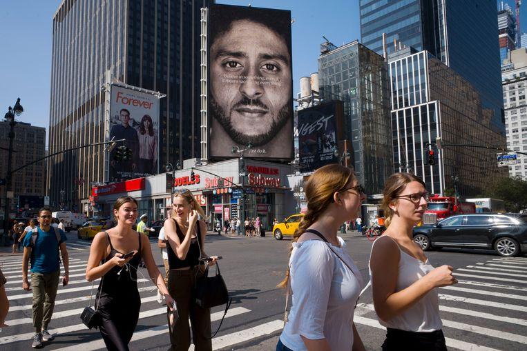 Mensen lopen in New York voorbij een Nike-advertentie met Colin Kaepernick. Beeld AP