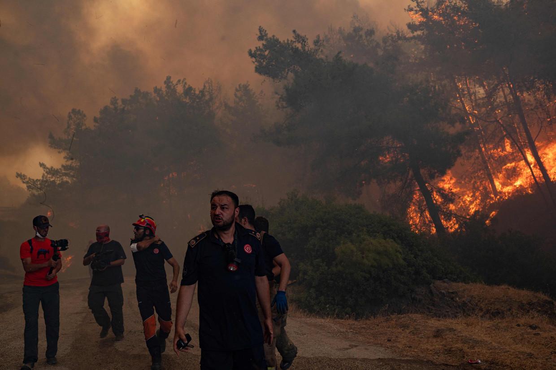 Brandweerlieden tussen de bosbranden bij het Turkse Marmaris. Beeld AFP