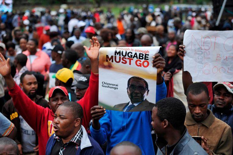 Demonstranten houden anti-Mugabe posters omhoog tijdens een protestmars op 18 november 2017, waarmee ze het aftreden van de president eisen. Beeld ANP