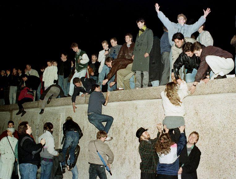Inwoners van Oost-Duitsland klimmen over de Berlijnse Muur, 10 november 1989. Beeld Reuters