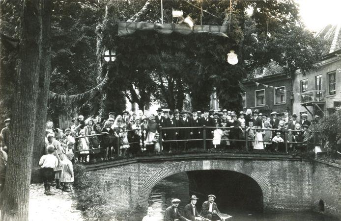 Op de brug over het Havik bij de Bloemendalse Binnenpoort viert Amersfoort in september 1923 het 25-jarig regeringsjubileum van koningin Wilhelmina. In het midden, in het zwart, het bestuur van de Oranjevereniging.