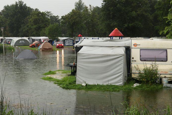 Tenten en caravans staan in het water op camping Klein Zwitserland. Stortbuien veroorzaakten gisteren in het noordoosten van Friesland veel wateroverlast.