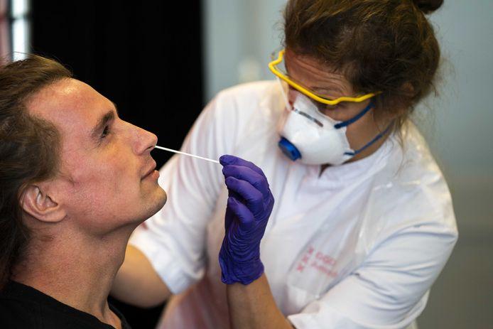 Een zorgmedewerker wordt getest op het coronavirus door medewerkers van de GGD Amsterdam.