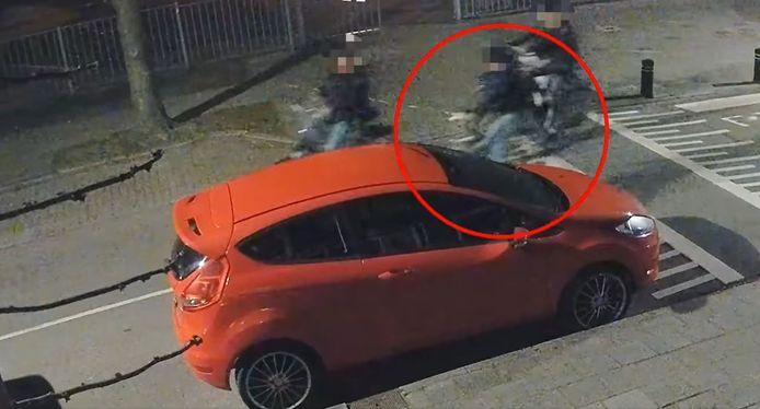 De rood omcirkelde persoon trapt de spiegel van deze auto kapot tijdens het fietsen.