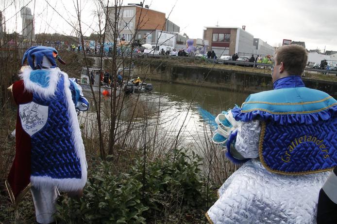Enkele carnavalsvierders kijken toe hoe hulpverleners de Dender met een sonarboot doorzoeken.