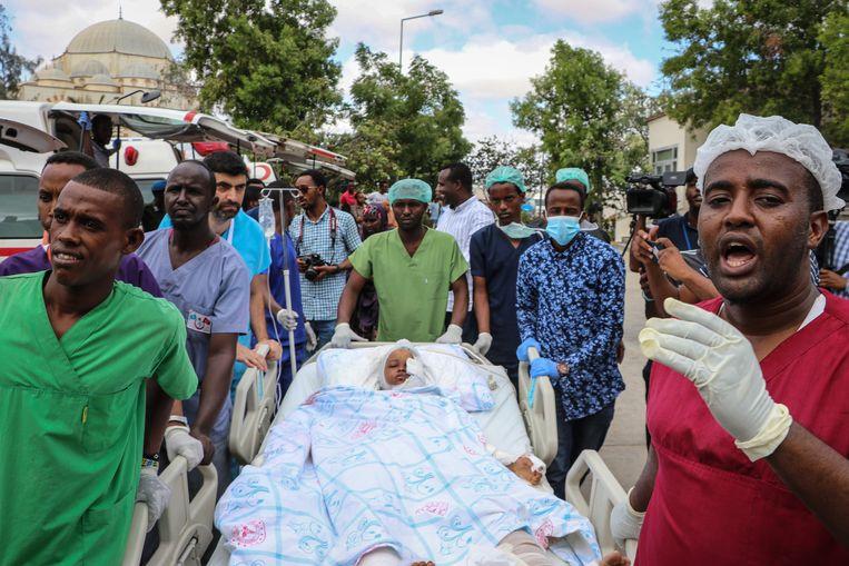 Een meisje wordt naar het ziekenhuis gebracht nadat zij gewond is geraakt door de aanslag van zaterdag in de Somalische hoofdstad Mogadishu. Beeld AFP