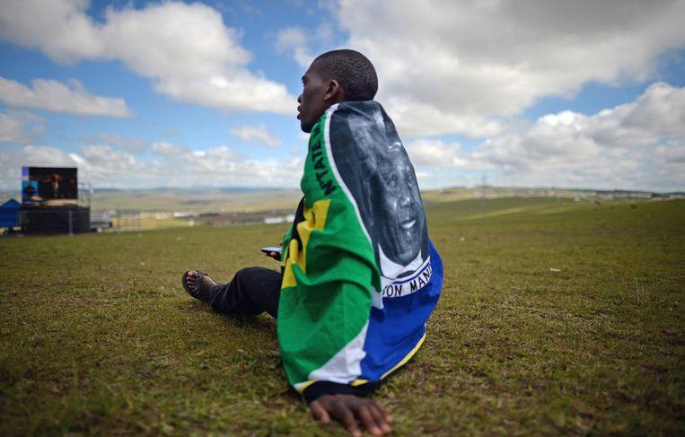 Een man met de Zuid Afrikaanse vlag om zijn schouders wacht tot de dienst voor Mandela begint. Beeld getty