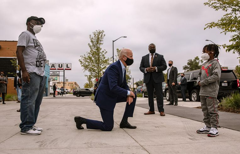Joe Biden maakt in Detroit, Michigan, een praatje met de zoon van een winkeluitbater (l.). Beeld NYT