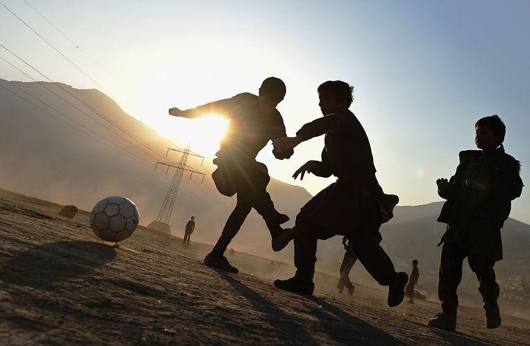 Kinderen spelen voetbal op een veld in Kabul. Beeld AFP