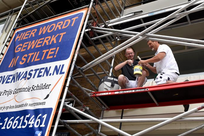 Danny Kema, met bril, en eigenaar Hans van Hartskamp zijn druk aan het werk op de steiger.  Kema is doof en werkt samen met Van Harskamp. Ze communiceren door middel van gebarentaal.