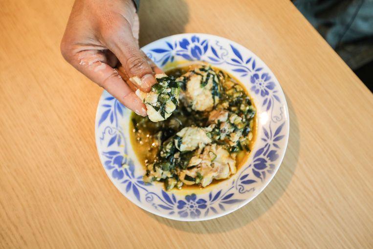 Eindresultaat van nigeriaanse stoofpot die je met handen eet met stukje broodmeel. Beeld Eva Plevier