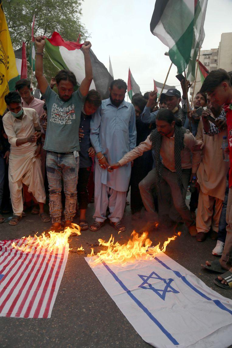 Betogers  in Karachi steken de Amerikaanse en Israëlische vlag in brand. Beeld EPA