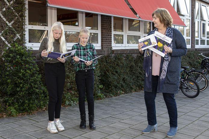 Leerlingen Marleen van Haarst (links)  en Tess Bokhove (rechts) uit groep 8 van de Oranjeschool in Vroomshoop ontvangen van Marijke Talen alsnog het werkboek overLeven als onderdeel van de interactieve presentatie van het gelijknamige boek over overlevenden van de Jodenvervolging.