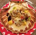 Het tussengerecht, gegrilde coquilles, meloesuitjes, bosui, shiitakes, spicy eiwitcrème, vleugje koriander is voorbereid in een schelp.