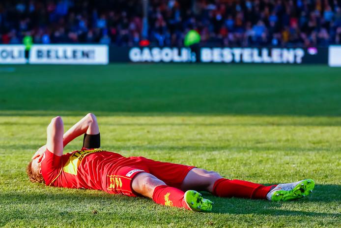 Eagles-speler Pieter Langedijk stort vol ongeloof op het gras na het laatste fluitsignaal.