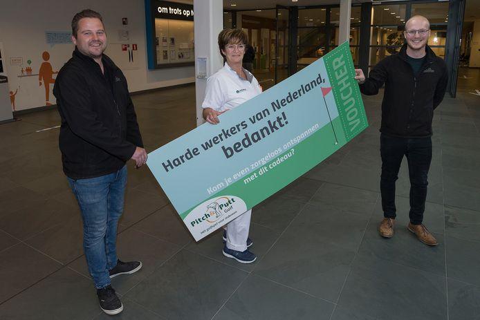 Niels van de Vondervoort (l) en Giel van Aarle reiken de golfvoucher uit aan Angelice Snelders  voor het zorgpersoneel in het Eindhovense Catharina-ziekenhuis.