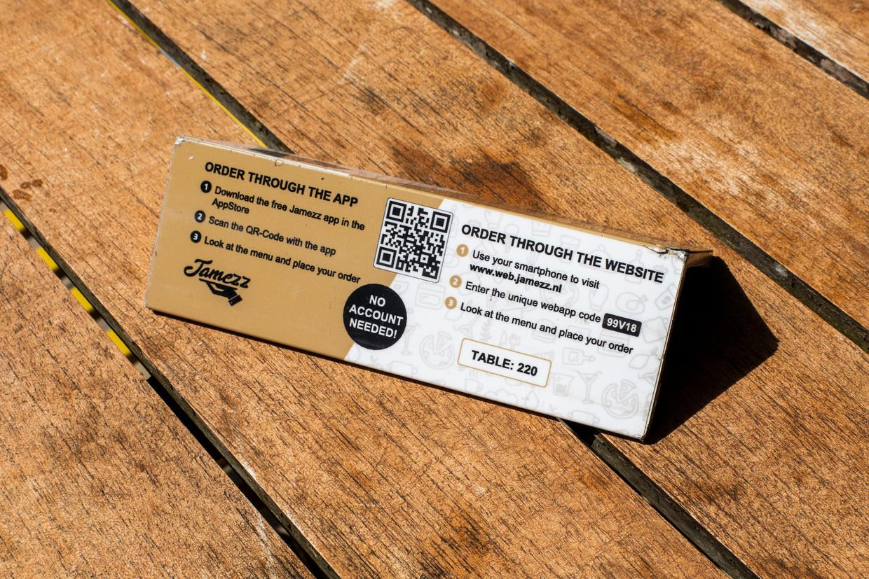 Een kaartje op een terrastafel maakt duidelijk dat de klant via een app of via een website moet bestellen.