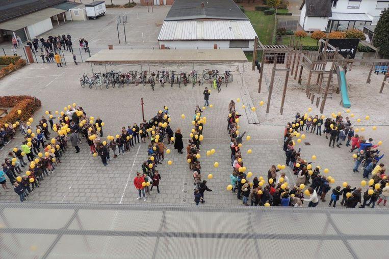 De leerlingen vormden de naam van Milo op de speelplaats.