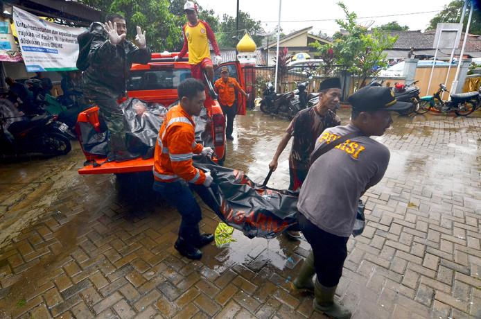 Reddingswerkers brengen een geborgen lichamen over naar het mortuarium.